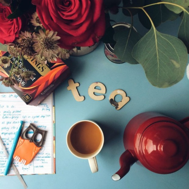 cup of tea with roses and red teapot