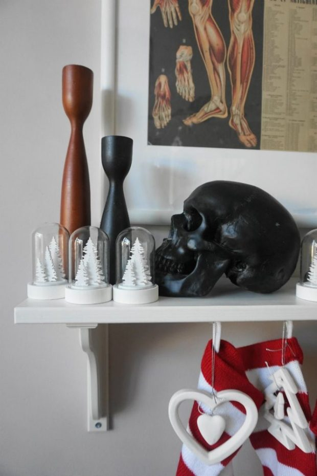 candlesticks and skulls on shelf as mantle