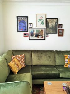 gallery wall bohemian living room with green velvet corner sofa