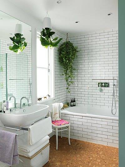 hanging plants in bathroom with subway metro tiles and dark grout with a cork floor