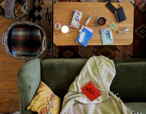 from above a boho cosy living room with blankets and books