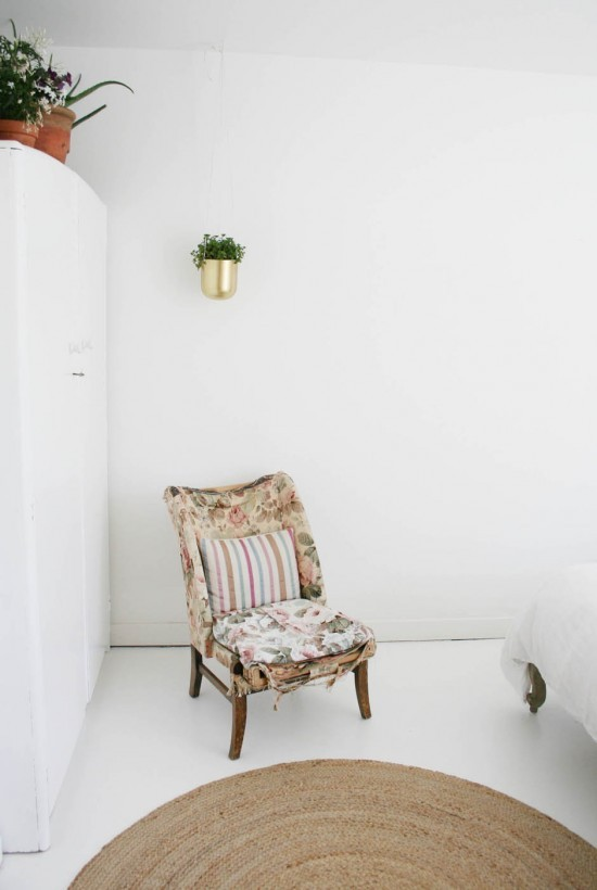 old chair white walls and hanging plants in bedroom